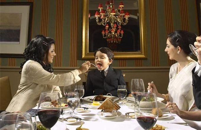 woman_feeding_boy_at_formal_dinner_1
